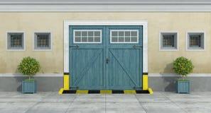 Alte Fassade mit hölzerner Garage des blauen Autos Stockfotos