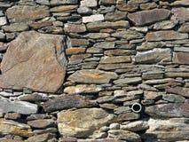 Alte Felsen-Wand mit Abflussrohr Lizenzfreies Stockfoto