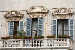 Alte Fenster mit hölzernen Fensterläden und Vorhang in Italien Stockfotografie