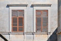 Alte Fenster mit hölzernen Fensterläden von der Sonne Lizenzfreie Stockfotos