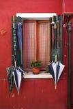 Alte Fenster mit Regenschirm auf bunten Häusern auf Burano Stockfotos