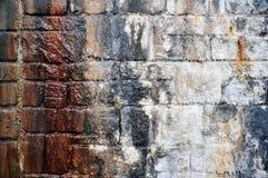 Alte Feuchtigkeit streifte Steinwand mit Weiß und Braun befleckte Farben Lizenzfreie Stockbilder