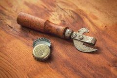 Alte Öffnerwerkzeug- und -bierkappen Stockbild