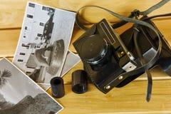 Alte Filmkamera mit Abdeckung, Fotos und Film auf einer Holzoberfläche Stockfoto