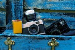 Alte Filmkamera mit Blitz, Filmkasten und alter mirorless schwarzer Kamera auf einem blauen hölzernen Hintergrund Stockfotos