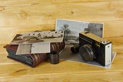 Alte Filmkamera mit dem Album, den Fotos und dem Film auf einer hölzernen Brandung Stockbild