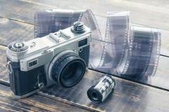 Alte Filmkamera, Schwarzweiss-Film und Filmstreifen auf einem hölzernen Stockbild