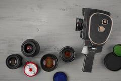 Alte Filmkamera und einige Linsen Stockbilder