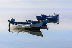 Alte Fischerboote mit hellen Farben an der Dämmerung auf dem See stockfotografie
