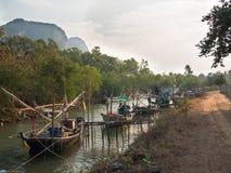 Alte Fischerboote stehen in Folge nahe dem Strand auf einem Hintergrund von Bergen Stockfotos