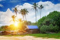 Alte Fischerboote und Hütten auf sandigem Strand und Sonnenuntergang Stockfotos