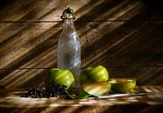 Alte Flasche mit grünen Äpfeln Lizenzfreie Stockfotos