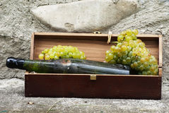 Alte Flasche weißer Wein mit Trauben Stockfotografie