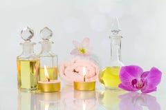 Alte Flaschen der Weinlese aromatische Öle mit gebrannten Kerzen, Blumen und weißem Tuch auf glatter weißer Tabelle auf weißem Hi Stockfoto