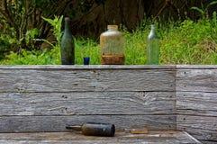 Alte Flaschen und Gläser warfen auf einen hölzernen Gartenzaun weg lizenzfreies stockfoto