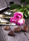 Alte Fotos zacken Rosen und Schokolade auf einem dunklen hölzernen Hintergrund aus Stockbilder