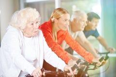 Alte Frau auf spinnendem Fahrrad in der Turnhalle Stockfoto