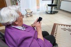 Alte Frau benutzt einen Smartphone lizenzfreie stockbilder