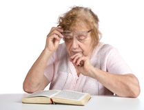 Alte Frau in den Gläsern liest das Buch Stockfotografie