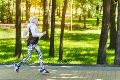 Alte Frau des glücklichen Sitzes, die entlang Bürgersteig unter grünen Bäumen läuft stockfotos