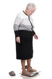 Alte Frau, die auf Badezimmerwaagen steht Lizenzfreies Stockbild
