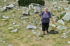 Alte Frau, die auf den Gebirgsgebieten wandert Lizenzfreie Stockbilder