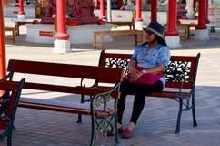 Alte Frau, die auf der Bank sitzt Stockbilder