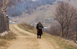 Alte Frau, die auf eine Bergdorfstraße geht Stockbild