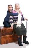 Alte Frau, die auf einem Kasten mit ihrer Enkelin sitzt Stockbild