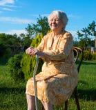 Alte Frau, die auf einem Stuhl mit einem Stock sitzt Stockbild