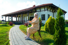 Alte Frau, die auf einem Stuhl mit einem Stock sitzt Stockfotografie