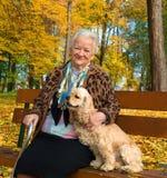Alte Frau, die auf einer Bank mit einem Hund sitzt Lizenzfreies Stockfoto