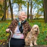 Alte Frau, die auf einer Bank mit einem Hund sitzt Stockfotos