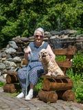 Alte Frau, die auf einer Bank mit einem Hund sitzt Stockbilder