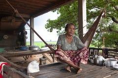 Alte Frau, die auf einer Hängematte sitzt stockfoto