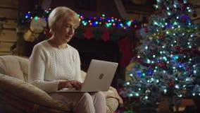 Alte Frau, die auf Laptop auf Heiliger Nacht nahe Baum simst stock footage