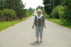 Alte Frau, die auf die Straße am sonnigen Tag geht Lizenzfreie Stockfotos