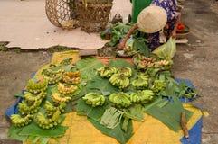 Alte Frau, die Bananen auf Straßenmarkt verkauft Lizenzfreie Stockbilder