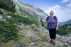 Alte Frau, die in den Bergen wandert Lizenzfreie Stockfotografie