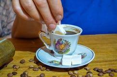 Alte Frau, die den türkischen Kaffee versüßt lizenzfreies stockbild