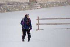 Alte Frau, die durch einen Blizzard geht Stockfoto