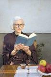 Alte Frau, die ein Buch im Hinterhof liest Lizenzfreies Stockfoto