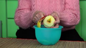 Alte Frau, die einem Apfel abzieht stock footage