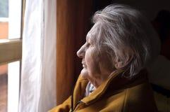 Alte Frau, die in einem Fenster schaut lizenzfreies stockfoto
