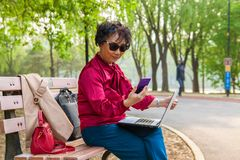 Alte Frau, die an einem Handy spricht lizenzfreie stockfotos