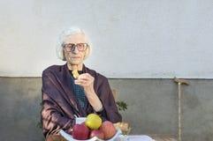 Alte Frau, die einen Snack im Hinterhof isst Lizenzfreie Stockfotos