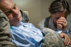 Alte Frau, die für am Ende kranken Ehemann betet Stockfoto
