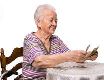 Alte Frau, die Geld zählt lizenzfreie stockfotografie