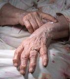 Alte Frau, die Handcreme aufträgt Stockbilder