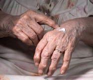 Alte Frau, die Handcreme aufträgt Stockfoto